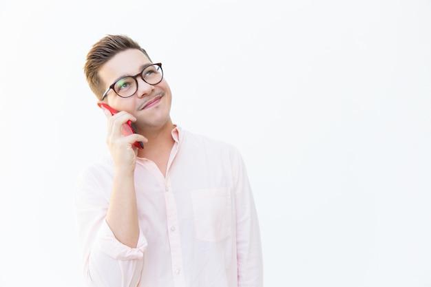 Heureux mec sympathique en lunettes parlant sur cellule