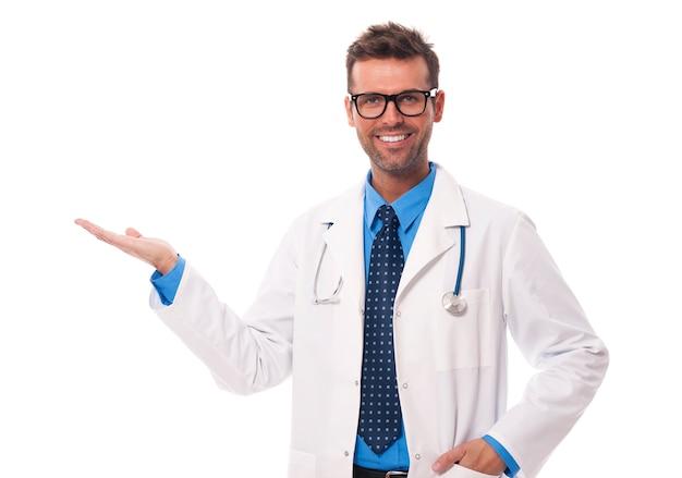 Heureux médecin portant des lunettes présentant quelque chose