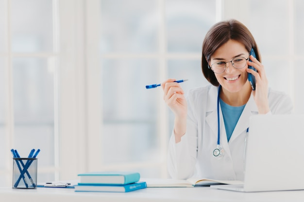 Heureux médecin professionnel concentré sur un ordinateur portable moderne, lit des informations utiles