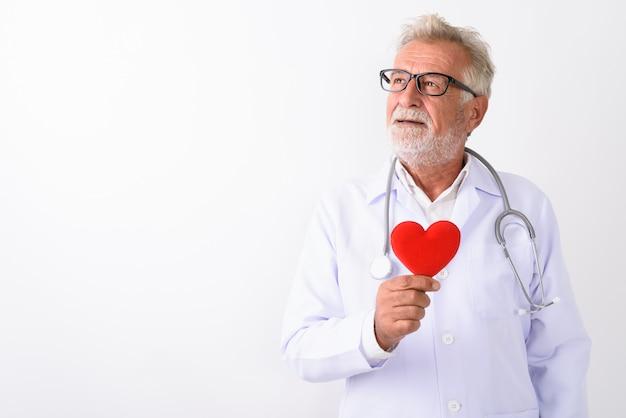 Heureux médecin senior homme barbu souriant tout en pensant et tenant coeur rouge sur blanc