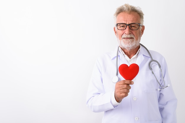 Heureux médecin senior homme barbu souriant tout en tenant coeur rouge sur blanc