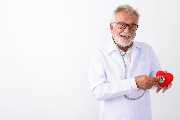 Heureux médecin senior homme barbu souriant tout en utilisant un stéthoscope sur coeur rouge sur blanc