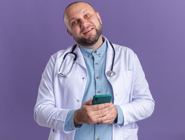 Heureux médecin de sexe masculin d'âge moyen portant une robe médicale et un stéthoscope tenant un téléphone portable isolé sur un mur violet