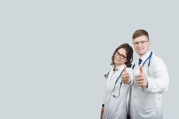 Heureux médecins. portrait de deux médecins en blouse blanche et lunettes montrant le pouce vers le haut sur fond gris isolé