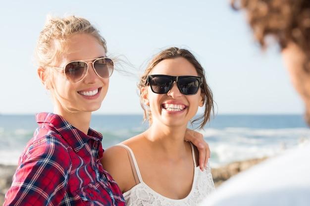 Heureux meilleurs amis souriants embrassant au bord de la mer