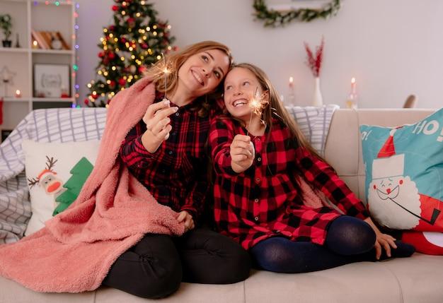 Heureux mère et fille tenant des cierges recouverts d'une couverture assis sur un canapé et profiter du temps de noël à la maison