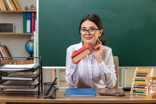Heureux de mettre la main sur la joue jeune enseignante portant des lunettes tenant un livre assis à table avec des outils scolaires en classe