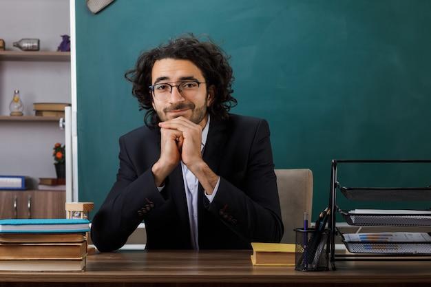 Heureux de mettre les mains sous le menton enseignant portant des lunettes assis à table avec des outils scolaires en classe