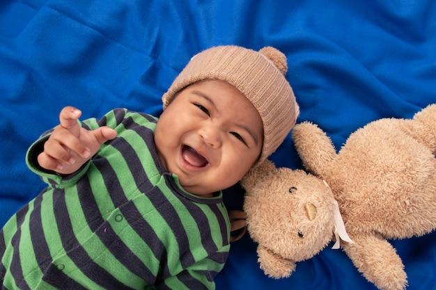 Heureux mignon petit bébé garçon couché sur une couverture bleue et souriant
