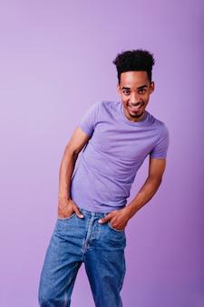 Heureux modèle drôle debout avec les mains dans les poches et souriant. mec africain insouciant aux cheveux bouclés exprimant son intérêt.