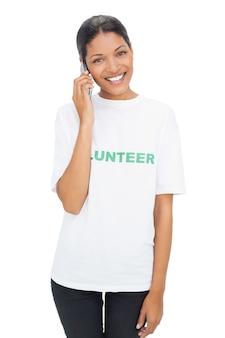 Heureux modèle portant des t-shirts bénévoles ayant un appel téléphonique