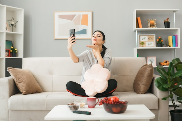 Heureux de montrer le geste de baiser jeune fille avec oreiller tenant et regardant le téléphone assis sur un canapé derrière une table basse dans le salon