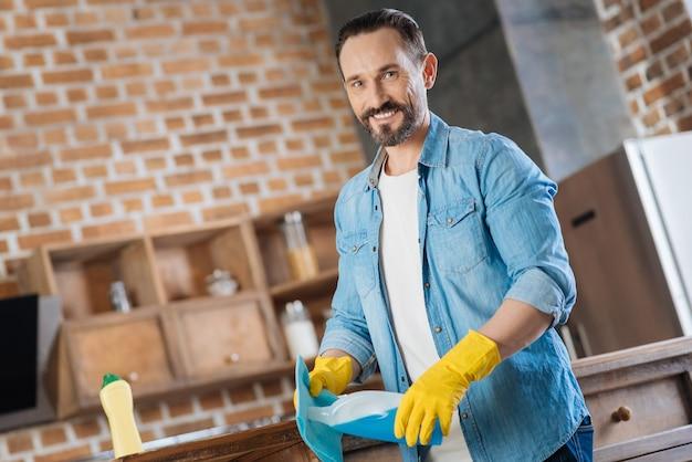 Heureux nettoyeur masculin gay transportant un nettoyant en se tenant debout sur l'arrière-plan flou et souriant