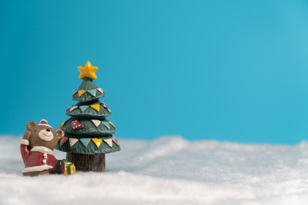 Heureux ours brun vêtue d'une robe de père noël avec boîte de cadeaux implantation sur la neige près de l'arbre de noël.