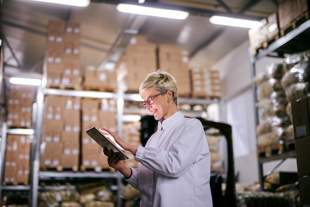Heureux ouvrier d'usine caucasienne à l'aide de tablette en se tenant debout dans l'entrepôt.
