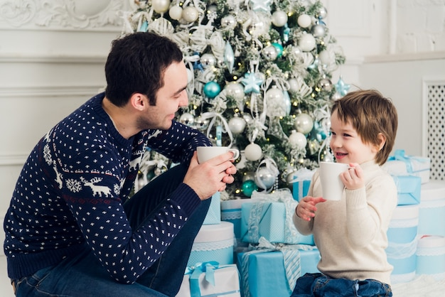 Heureux papa et fils avec des tasses de thé à noël
