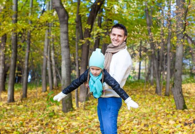 Heureux papa et petite fille s'amuser dans le parc sur une journée ensoleillée d'automne