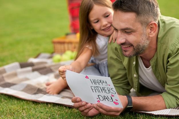 Heureux papa recevant une carte postale faite à la main de son père fille et de sa petite fille en train de pique-niquer