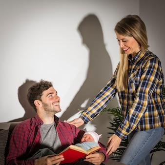Heureux parents avec bébé et livre