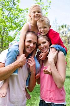 Heureux parents donnant à leurs enfants un tour de ferroutage