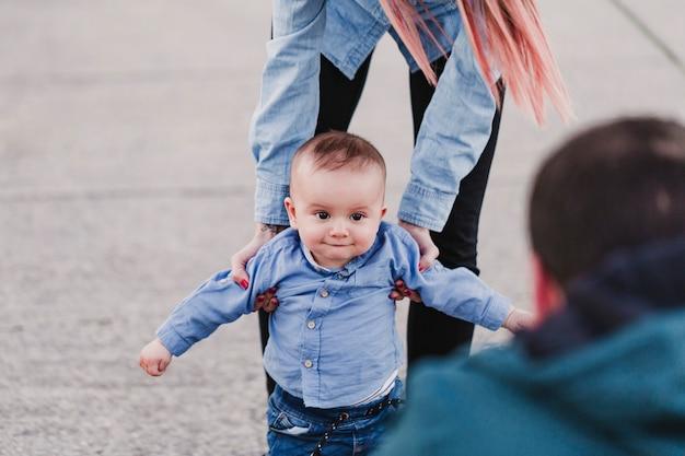 Heureux parents élégants, main dans la main avec bébé et marche dans la rue, moment familial tendre.