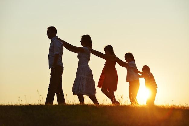 Heureux parents avec enfants à l'extérieur au coucher du soleil