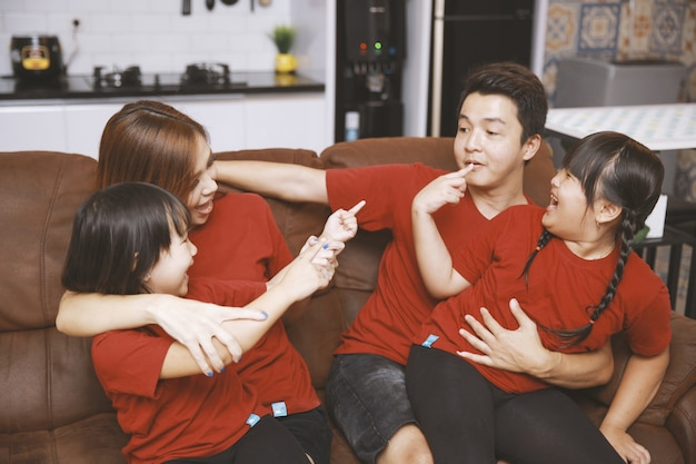 Heureux parents et enfants s'amusant assis ensemble sur un canapé joyeux jeune couple parlant et riant jouant à un jeu avec deux petites filles dans le salon à la maison activité amusante en famille