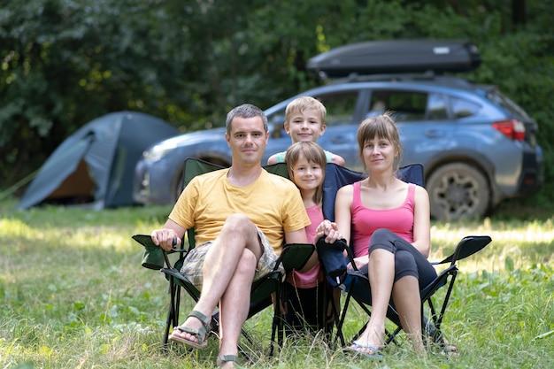 Heureux parents et enfants se reposant ensemble au camping.