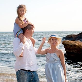 Heureux parents de famille et petite fille en randonnée près de la mer