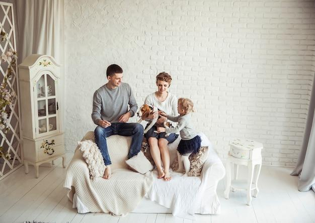 Heureux parents, fille de cinq ans avec un chien assis sur le canapé dans le salon
