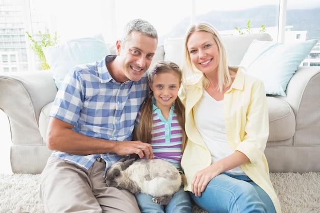 Heureux parents et fille avec le lapin dans le salon