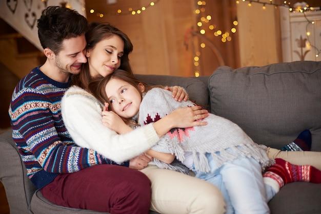 Heureux parents avec fille se détendre sur le canapé
