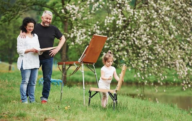 Heureux parents. grand-mère et grand-père s'amusent à l'extérieur avec leur petite-fille. conception de peinture