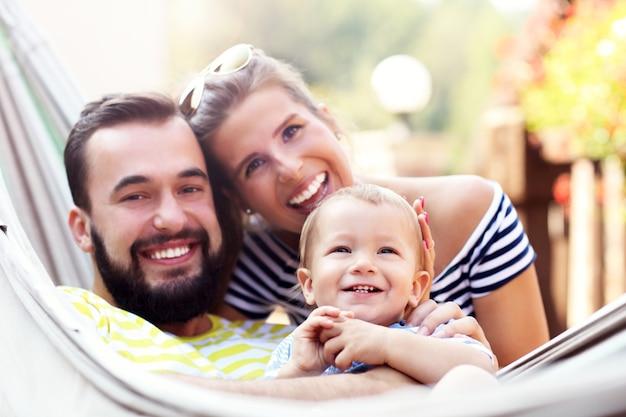 Heureux parents jouant avec leur petit garçon dans un hamac à l'extérieur