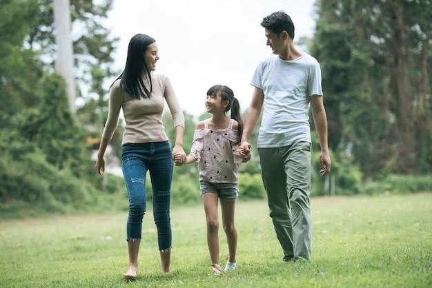 Heureux parents et leur fille marchant dans le parc, notion de famille heureuse.