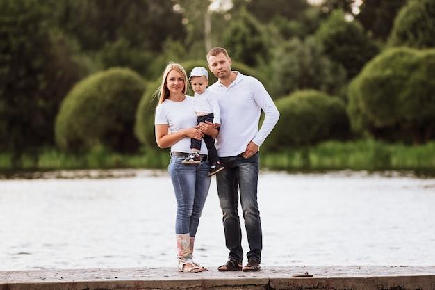 Heureux parents avec leur petit-fils debout sur la jetée. le concept de bonheur familial