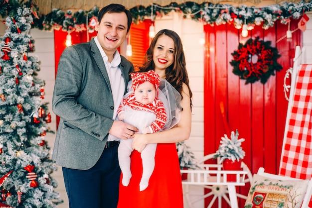 Heureux parents avec leur petite fille dans des vêtements élégants ensemble dans une salle de vacances décorée avec un arbre de noël et une couronne