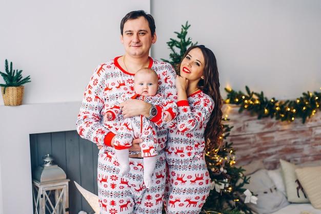 Heureux parents avec leur petite fille en vêtements de vacances avec des cerfs imprimés et des flocons de neige dans une chambre confortable avec un arbre de noël, des cadeaux et des lumières de noël. concept de vacances de noël et de nouvel an.