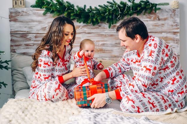 Heureux parents avec leur petite fille en vêtements de vacances avec des cerfs imprimés et des flocons de neige déballant le cadeau de noël dans une chambre confortable
