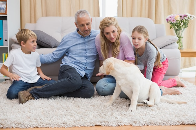 Heureux parents et leurs enfants sur le plancher avec chiot