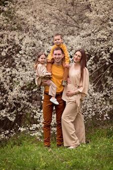 Heureux parents maman enceinte et papa, fille et fils sur le fond des arbres en fleurs.