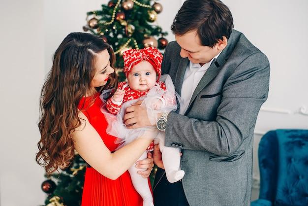 Heureux parents et petit bébé dans des vêtements élégants ensemble dans une salle de noël décorée.