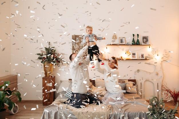 Heureux parents avec petit enfant mignon debout ensemble dans un magnifique studio, étreignant, regardant devant et posant