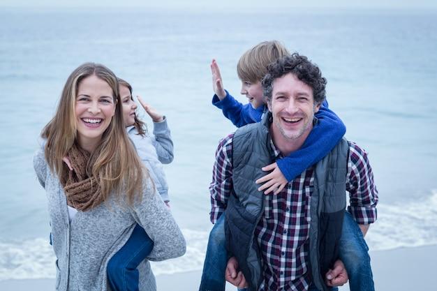 Heureux parents portant des enfants au bord de la mer