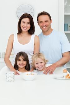 Heureux parents posant avec leurs enfants dans la cuisine