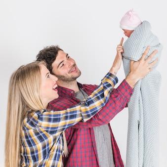Heureux parents regardant bébé dans les mains