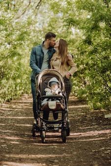 Heureux parents s'embrassent en marchant dans le parc avec un bébé dans une poussette