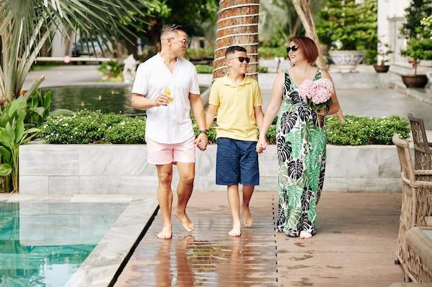Heureux parents se tenant la main de leur fils préadolescent lors de la marche sur le territoire de l'hôtel spa