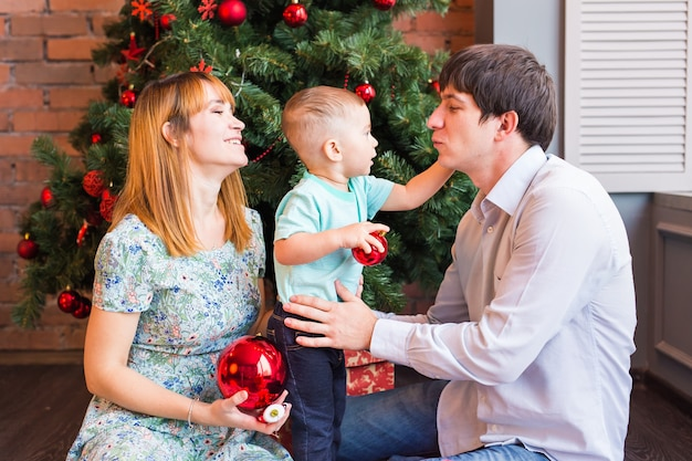 Heureux parents souriants et enfant à la maison pour célébrer noël
