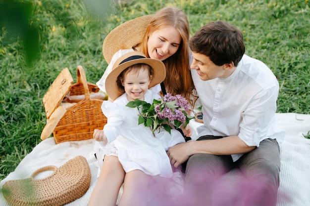 Heureux parents souriants avec leur fille lors d'un pique-nique une famille sur une pelouse verte dans un champ